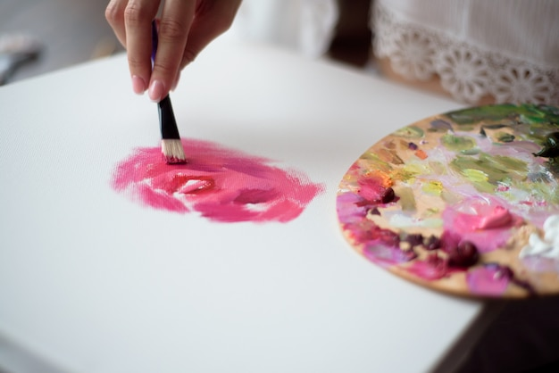 Artista de mulher desenhando sua foto na lona com cores de óleo em casa