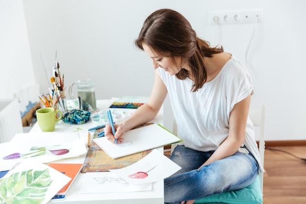 Artista de mulher feliz e atraente fazendo esboços em oficina