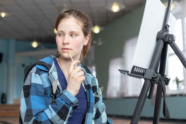 Artista de mulher jovem adolescente em processo de pintura com tintas a óleo.