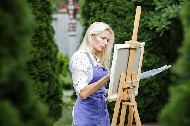 Artista de mulher loira bonita com um pincel na mão desenha sobre uma tela no jardim.