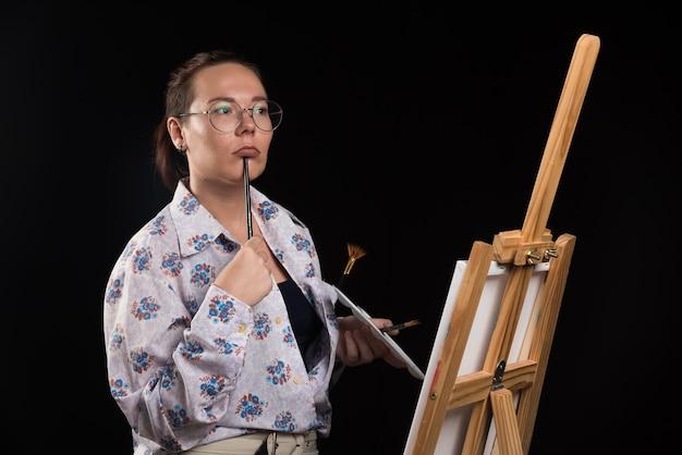 Artista de mulher segura um pincel na boca e pensa sobre fundo preto.