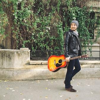 Artista de rua atraente jovem com seu violão