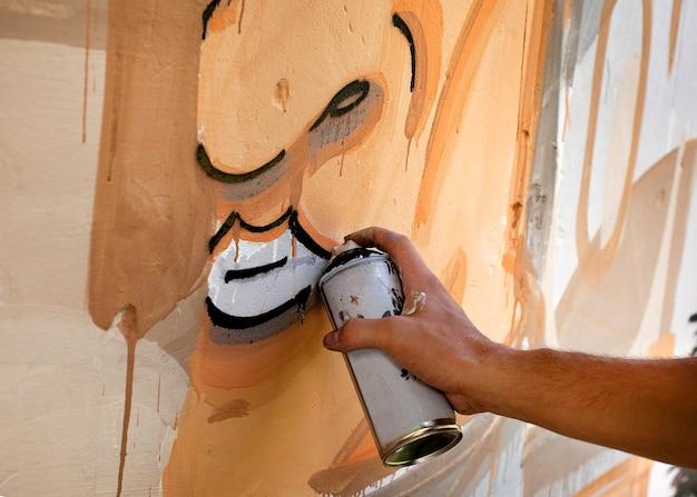 Artista de rua pintando graffiti em uma parede.