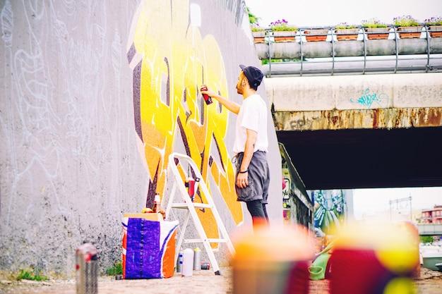 Artista de rua pintando um grafite colorido em uma parede cinza sob a ponte