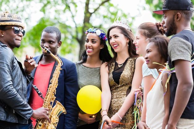Artista de rua tocando saxofone para grupo de festa multi-étnica