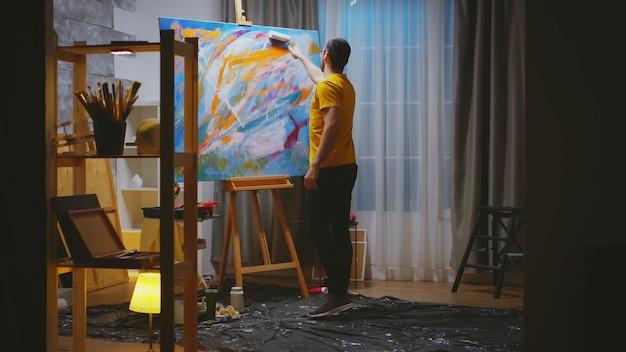 Artista de sucesso pintando com rolo em uma tela grande na oficina de arte.