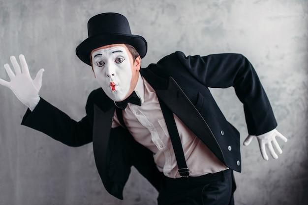 Artista de teatro pantomima posando, imitando um homem com máscara de maquiagem branca.