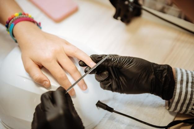 Artista de unhas. adolescente estilosa e moderna usando pulseiras brilhantes indo para a unha artista depois da escola