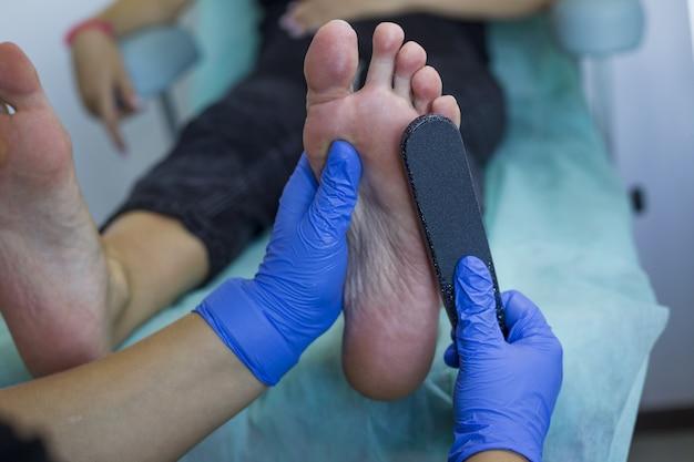 Artista de unhas em salão de beleza fazendo pedicure para os pés dos clientes.