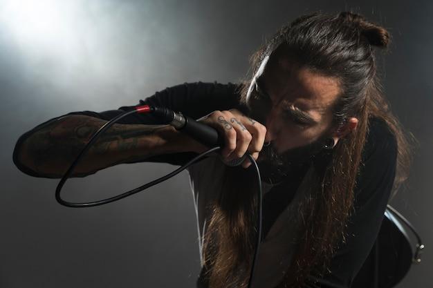Artista de visão frontal cantando no palco