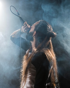 Artista de vista lateral cantando no palco e efeito de fumaça