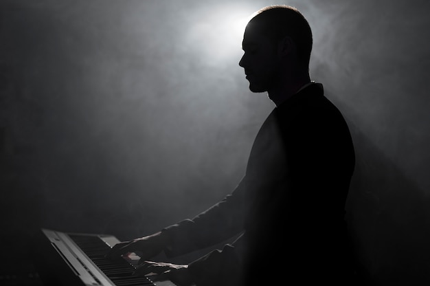 Artista de vista lateral tocando fumaça de piano e efeitos de sombras