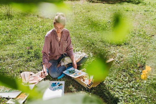 Artista desenhando flores com tintas a óleo ao ar livre, pintora