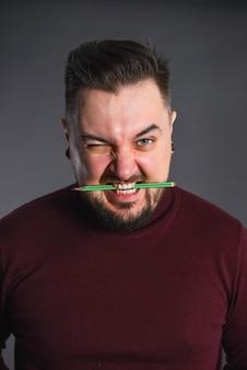 Artista designer, pronto para trabalhar e segura um lápis nos dentes.