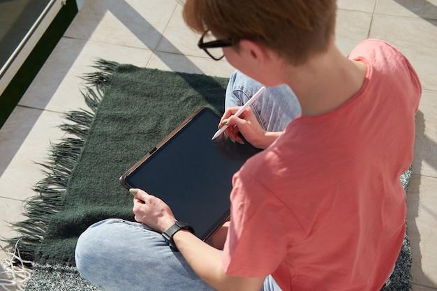 Artista digital garota desenhando sobre tablet enquanto está sentado na varanda ensolarada. trabalho freelance