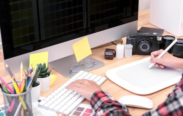 Artista do designer gráfico que usa a tabuleta de gráficos que tira seu trabalho na mesa no escritório.