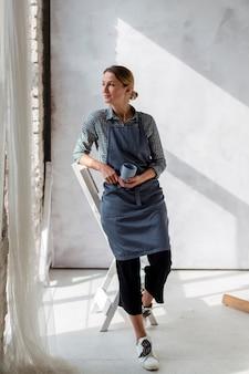 Artista em avental posando com caneca