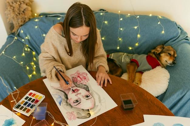 Artista em cena pintando um retrato sentado ao lado de um cachorro