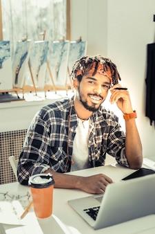 Artista empolgado. jovem artista inexperiente sentindo-se extremamente alegre e animada enquanto trabalha