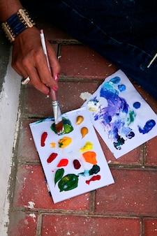 Artista esfregando o pincel em gotas de tintas a óleo coloridas