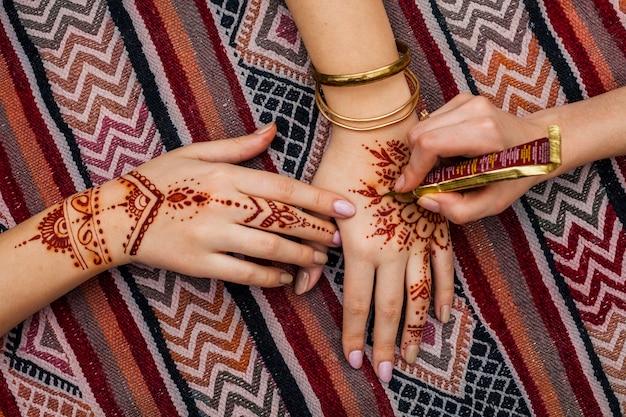 Artista fazendo mehndi na mão da mulher na mesa brilhante