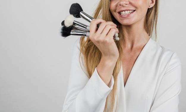 Artista feliz segurando maquiagem pincéis