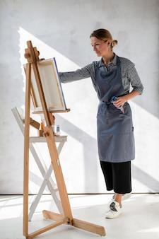 Artista fêmea que pinta no avental