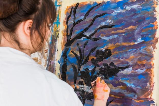 Artista feminina de desenho na lona com pincelada preta
