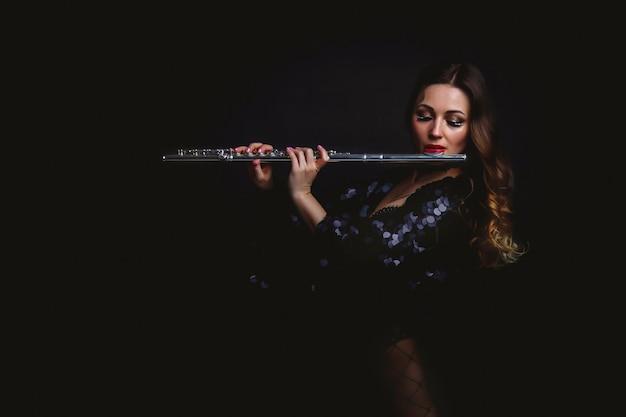 Artista feminina de terno com flauta em fundo preto
