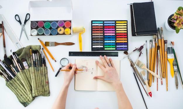 Artista feminina desenhando o esboço gráfico no caderno com lápis na galeria de arte, seu local de trabalho. foto de vista superior de ferramentas artísticas, deitada na mesa de trabalho: coleção de guache, giz de cera e pincel.