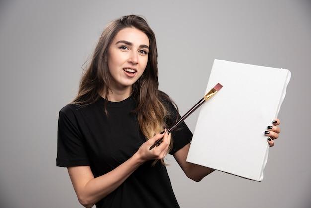 Artista feminina na camisa preta, pintura sobre tela.