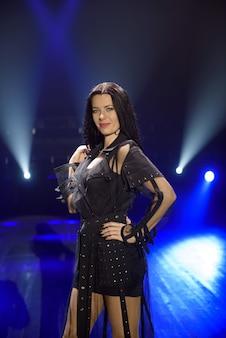 Artista feminina no palco em fundo escuro, fumaça, holofotes azuis