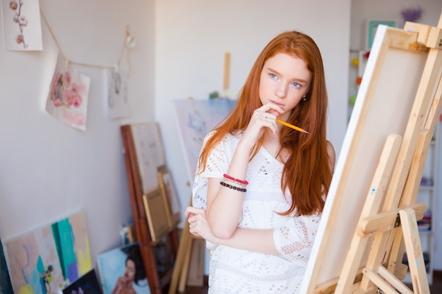 Artista feminina pensativa e atraente com um lindo cabelo ruivo comprido pensando e fazendo