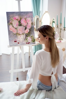 Artista feminina pinta uma imagem sobre tela com tintas a óleo em casa, vista traseira.
