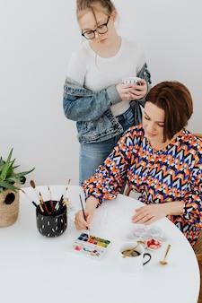 Artista feminina pintando enquanto a filha está assistindo