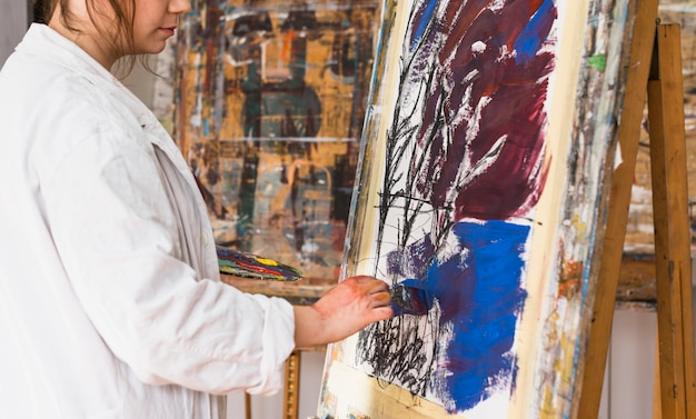 Artista feminina, pintura com pincel sobre tela na oficina