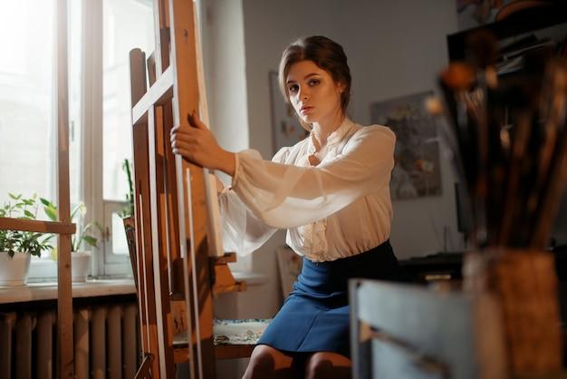 Artista feminina trabalha no cavalete em estúdio.