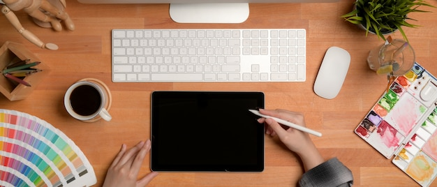 Artista feminina trabalhando na mesa de madeira com tablet digital, computador, ferramentas de pintura e decorações