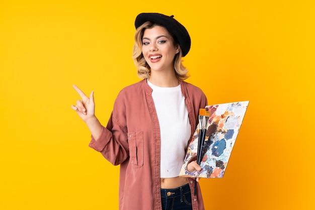 Artista garota segurando uma paleta apontando o dedo para o lado