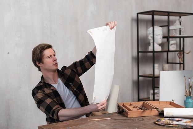 Artista homem olhando para sua pintura