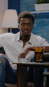 Artista inválido afro-americano, projetando o desenho de um vaso branco no espaço da oficina. jovem negro sentado em uma cadeira de rodas trabalhando em uma obra-prima moderna para uma galeria de sucesso