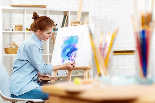 Artista jovem bonita desenho pintura abstrata em um cavalete