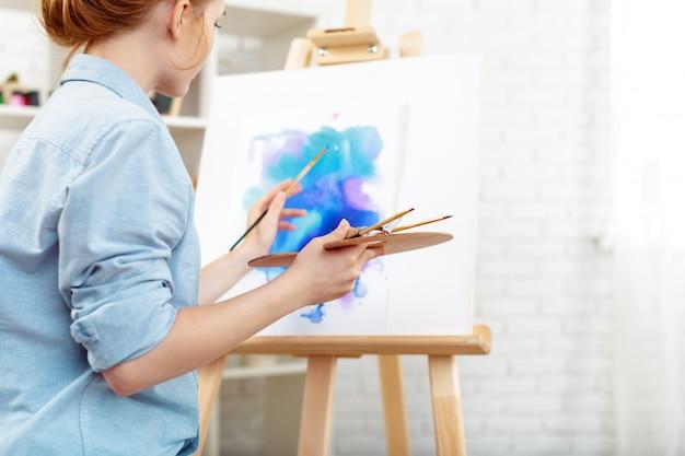 Artista jovem mulher bonita desenho pintura abstrata em um cavalete