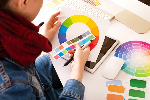 Artista jovem mulher na jaqueta jeans desenhando algo sobre tablet gráfico no escritório