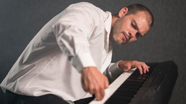 Artista lateral tocando várias oitavas no piano digital