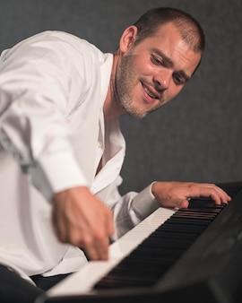 Artista lateralmente tocando várias oitavas no piano digital