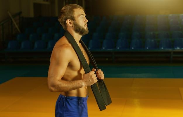Artista marcial com torso nu e faixa preta em ginásio esportivo