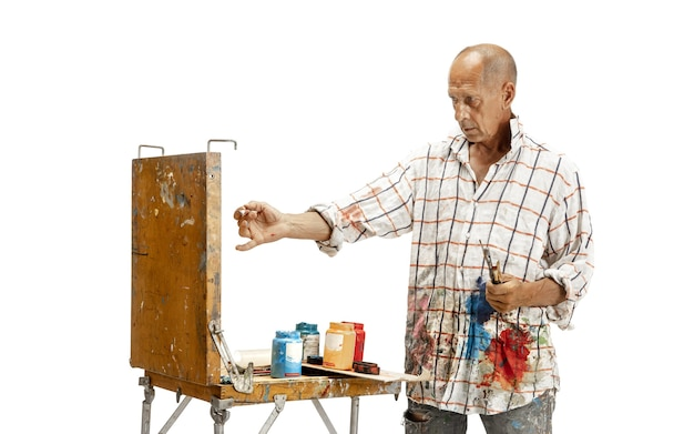 Artista masculino, caucasiano, pintor no trabalho, isolado no fundo branco do estúdio. pintar, trabalhar com cores, fazer composição. conceito de ocupação profissional, trabalho, emprego, produção artesanal.