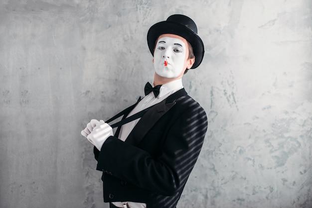 Artista masculino de mímica com máscara de maquiagem branca. ator de comédia de terno, luvas e chapéu.