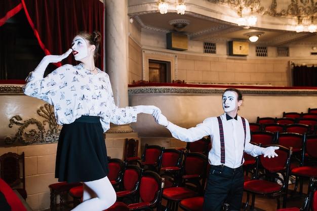 Artista masculino mime segurando a mão do mime feminino tímido no auditório